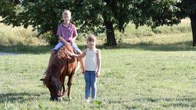 Счастливые мальчик и маленькая девочка с пони акции видеоматериалы