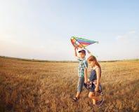 Счастливые мальчик и маленькая девочка с ярким змеем на луге Стоковая Фотография RF