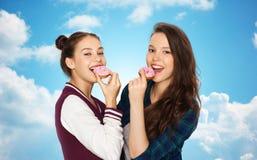 Счастливые милые девочка-подростки есть donuts Стоковые Изображения RF