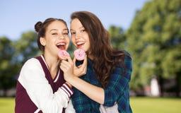 Счастливые милые девочка-подростки есть donuts Стоковое Изображение RF