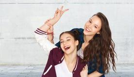 Счастливые милые девочка-подростки показывая знак руки мира стоковая фотография