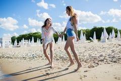 Счастливые милые женщины держа руки идя на пляж Стоковое Фото