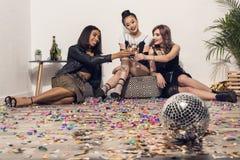 Счастливые многонациональные девушки сидя и выпивая шампанское на партии Стоковые Фотографии RF