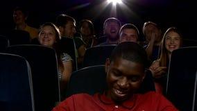 Счастливые многонациональные молодые человеки смотря кино в акции видеоматериалы
