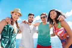 Счастливые моложавые девушки и парни ослабляя на лете приставают к берегу Стоковое Фото