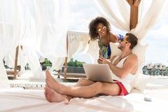 Счастливые моложавые пары в влюбленности отдыхая на пляже Стоковая Фотография