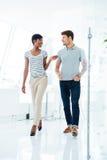 Счастливые молодые бизнесмены идя коридор в офисе Стоковые Изображения RF