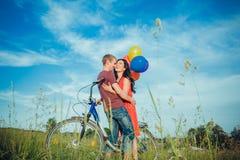 Счастливые молодые взрослые пары в влюбленности на поле 2, человек и женщина усмехаясь и отдыхая после катания велосипеда Стоковые Фотографии RF