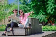 Счастливые молодые городские девушки в европейском городе Кавказские туристы имея потеху совместно outdoors Стоковые Изображения RF