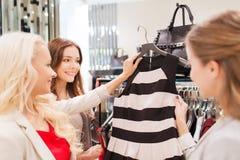 Счастливые молодые женщины выбирая одежды в моле Стоковые Фотографии RF
