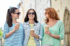 Счастливые молодые женщины выпивая кофе на улице города Стоковое Изображение RF