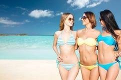 Счастливые молодые женщины в бикини на пляже лета Стоковые Фото