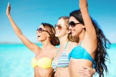 Счастливые молодые женщины в бикини на пляже лета Стоковые Изображения