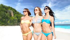 Счастливые молодые женщины в бикини на пляже лета Стоковое фото RF