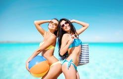 Счастливые молодые женщины в бикини представляя на лете приставают к берегу Стоковое Фото