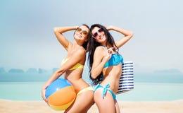Счастливые молодые женщины в бикини представляя на лете приставают к берегу Стоковые Фото