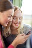Счастливые молодые женщины в шине перемещения с smartphone Стоковые Изображения