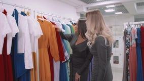 Счастливые молодые женщины идя вдоль магазина моды, продажи, защиты интересов потребителя и концепции людей акции видеоматериалы