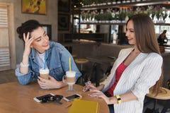 Счастливые молодые женщины обсуждая что-то в кафе Стоковые Изображения RF
