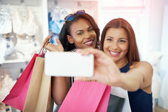 Счастливые молодые женщины принимая selfie пока ходящ по магазинам Стоковое Фото