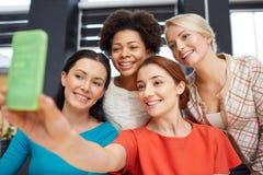 Счастливые молодые женщины принимая selfie с smartphone Стоковая Фотография RF