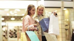Счастливые молодые женщины с хозяйственными сумками в моле сток-видео