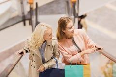 Счастливые молодые женщины с хозяйственными сумками в моле Стоковое фото RF