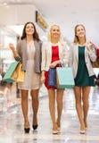 Счастливые молодые женщины с хозяйственными сумками в моле Стоковое Изображение