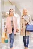 Счастливые молодые женщины с хозяйственными сумками в моле Стоковое Фото