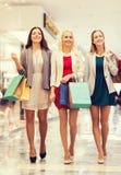 Счастливые молодые женщины с хозяйственными сумками в моле Стоковая Фотография