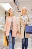 Счастливые молодые женщины с хозяйственными сумками в моле Стоковые Фотографии RF