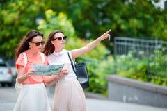 Счастливые молодые женщины с хозяйственными сумками идя вдоль улицы города Продажа, защита интересов потребителя и концепция люде Стоковые Изображения
