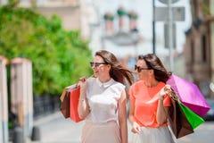 Счастливые молодые женщины с хозяйственными сумками идя вдоль улицы города Продажа, защита интересов потребителя и концепция люде Стоковые Фотографии RF