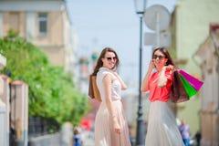 Счастливые молодые женщины с хозяйственными сумками идя вдоль улицы города Продажа, защита интересов потребителя и концепция люде Стоковая Фотография