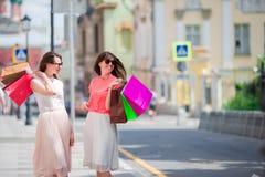Счастливые молодые женщины с хозяйственными сумками идя вдоль улицы города Продажа, защита интересов потребителя и концепция люде Стоковое Изображение RF