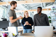 Счастливые молодые коллеги говоря друг с другом Стоковая Фотография RF