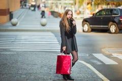 Счастливые молодые красивые женщины держа хозяйственные сумки, идя далеко от магазина на улице города Продажа, защита интересов п Стоковое Фото