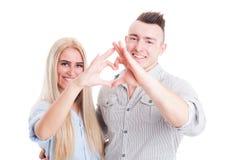 Счастливые молодые красивые пары делая форму шестка Стоковые Изображения
