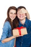 Счастливые молодые красивые пары изолированные на белой предпосылке с подарком в руке стоковая фотография rf