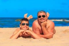 Счастливые молодые мальчик и человек на море приставают к берегу Стоковые Изображения