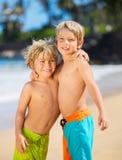 Счастливые молодые парни играя на пляже на летних каникулах Стоковое фото RF