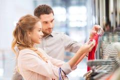 Счастливые молодые пары выбирая платье в моле Стоковое фото RF