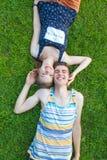 Счастливые, молодые пары лежа в солнце Стоковые Фотографии RF