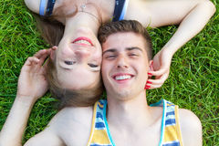 Счастливые, молодые пары лежа в солнце Стоковое Изображение RF