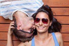 Счастливые молодые пары лежа на деревянном поле Стоковые Фото