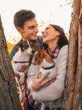 Счастливые молодые пары держа собак в парке и усмехаться стоковые фотографии rf