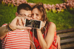 Счастливые молодые пары имея потеху на парке и принимая selfie наслаждаясь солнечным днем снаружи Стоковая Фотография