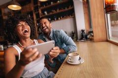 Счастливые молодые пары имея потеху с телефоном на кафе Стоковое Изображение