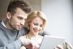 Счастливые молодые пары используя цифровую таблетку в кафе Стоковая Фотография