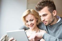 Счастливые молодые пары используя цифровую таблетку в кафе Стоковое Изображение